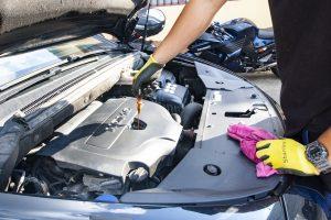 איש עם כפפה צהובה בודק שמן לרכב